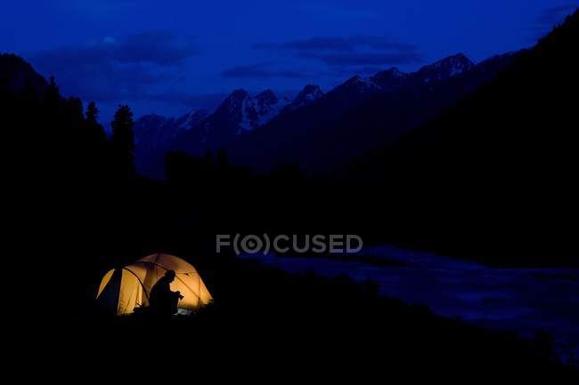 Lidderwat Kashmir India; Tenting In The Wilderness during nighttime with person in camp — Stock Photo