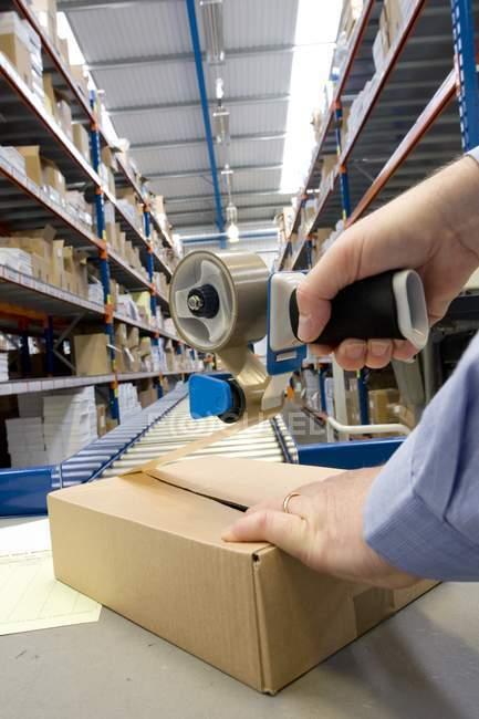 Обрезанное изображение мужской упаковки рук на складе рядом с большим ленточным конвейером — стоковое фото