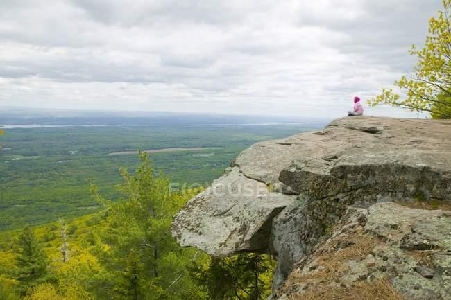 Donna sola seduta sulla scogliera — Foto stock