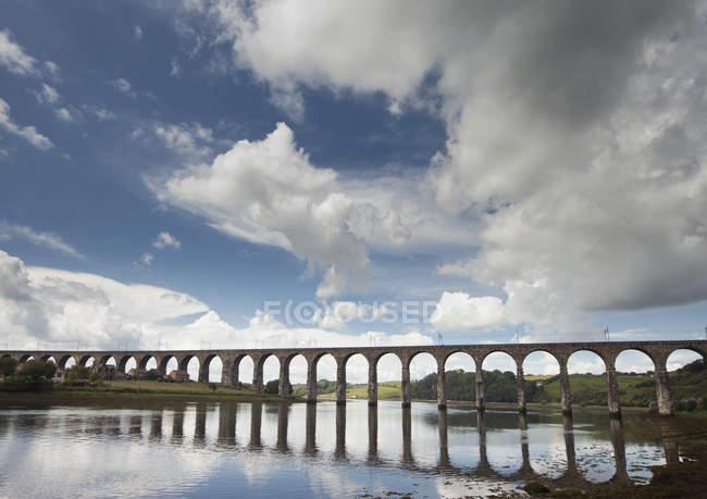 Un puente reflejado en el agua - foto de stock