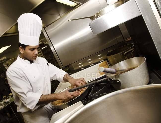 Chef preparando la comida en la cocina - foto de stock