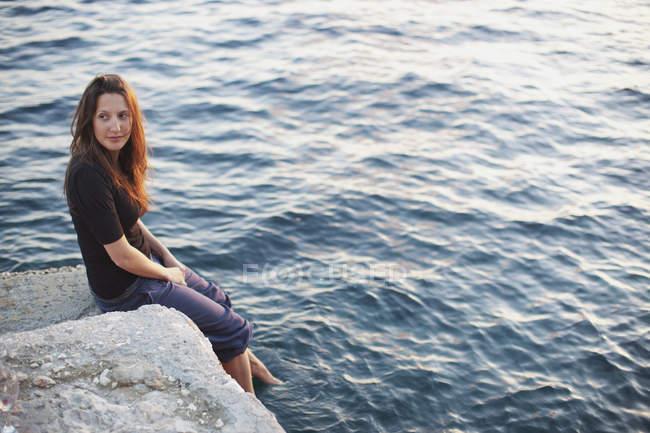 Ein Mädchen, das auf einem Felsen sitzt und seine Füße ins Wasser taucht; hvar, Kroatien — Stockfoto