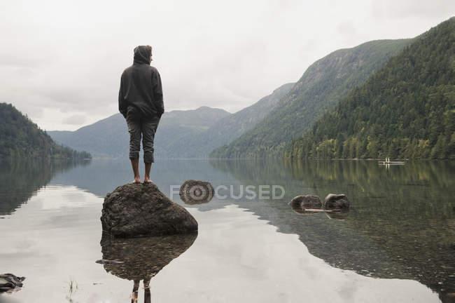 Jeune homme se tient sur le roc — Photo de stock