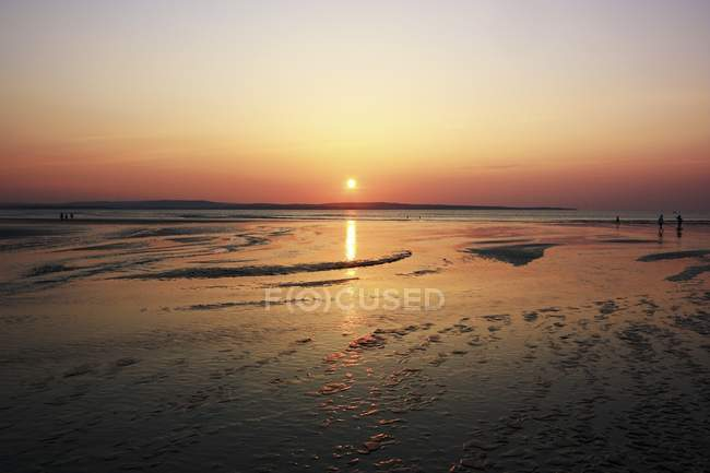 Sunset over sandy beach — Stock Photo