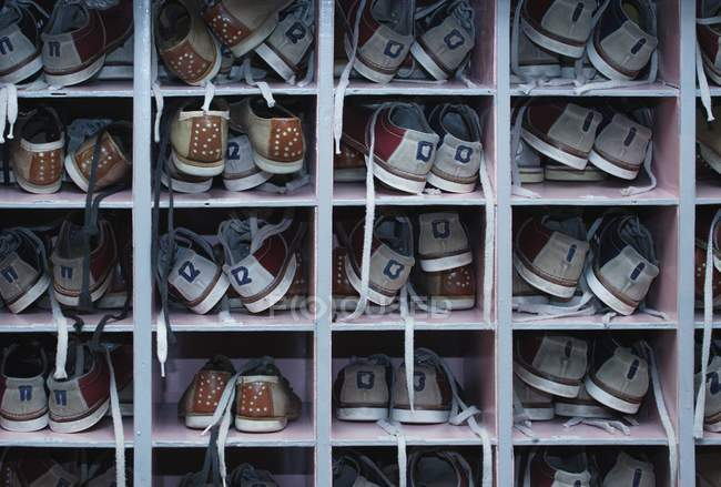 Shelf with all sizes bowling shoes for hire — Stock Photo