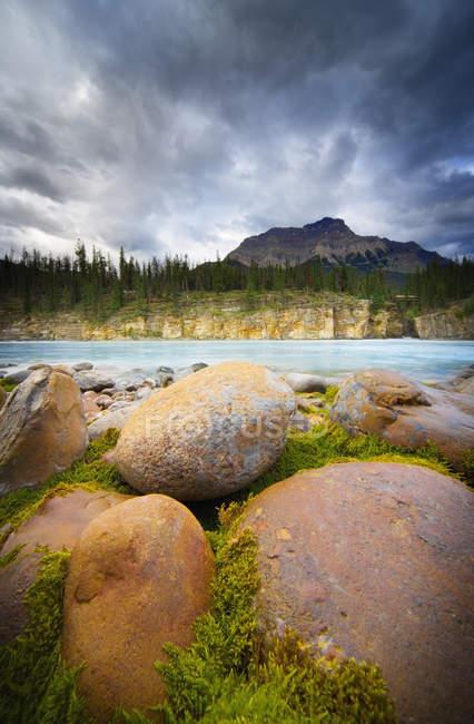 Litorale roccioso con nuvole — Foto stock
