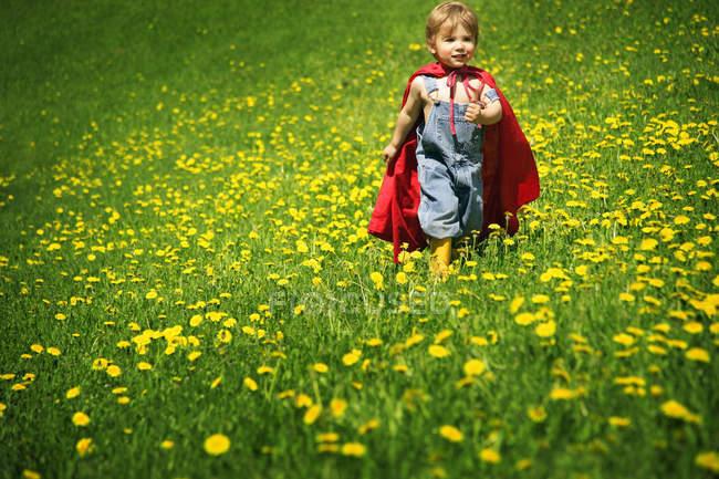 Garçon jouant au Cap comme super-héros dans le champ vert — Photo de stock