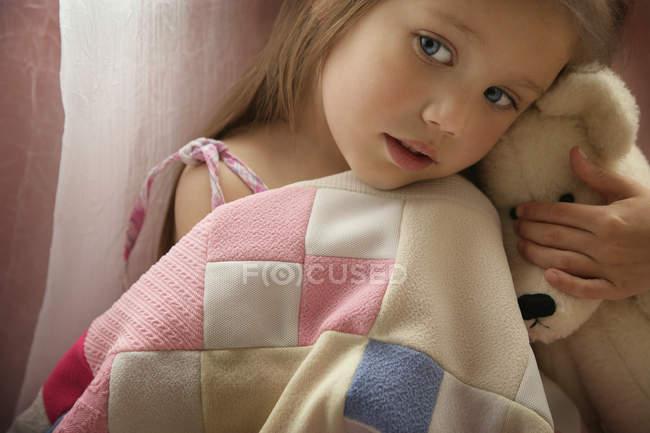 Mädchen mit Teddybär mit Decke drinnen — Stockfoto