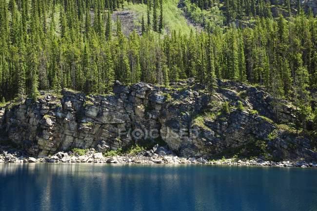 Lago de montaña con acantilado rocoso - foto de stock
