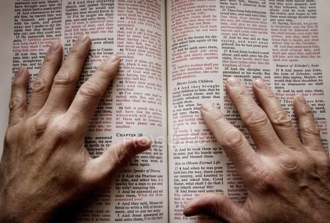 Hände auf aufgeschlagene Bibel — Stockfoto
