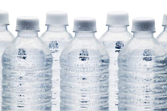 Row of transparent water bottles on white background — Stock Photo