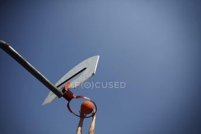 Niedrigen Winkel Ansicht der Person spielt Basketball gegen blauen Himmel — Stockfoto