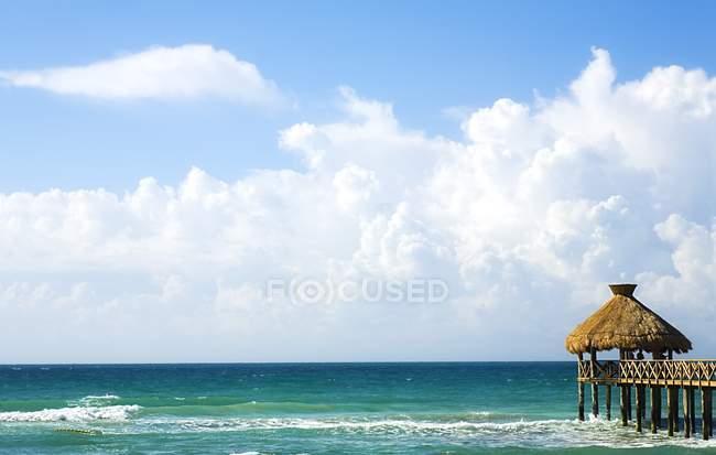 Quai avec vue sur mer avec des nuages blancs — Photo de stock
