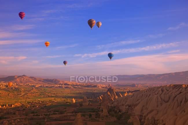 Globos de aire caliente flotando sobre tierras baldías - foto de stock
