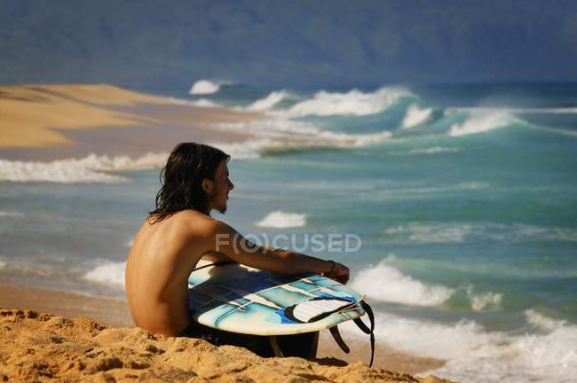 Серфингист, сидящий на пляже — стоковое фото