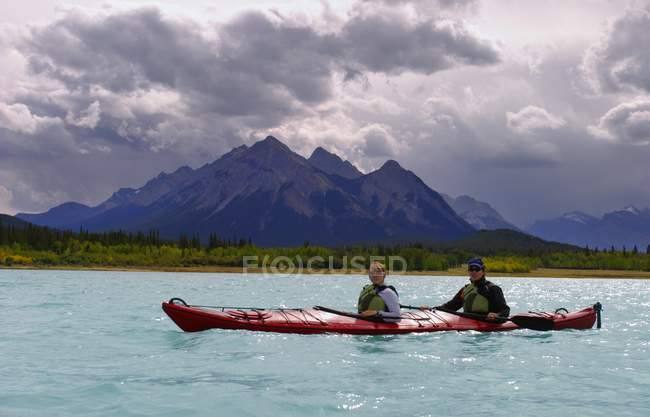 Paddlers On A Lake over water with mountain on background — Stock Photo