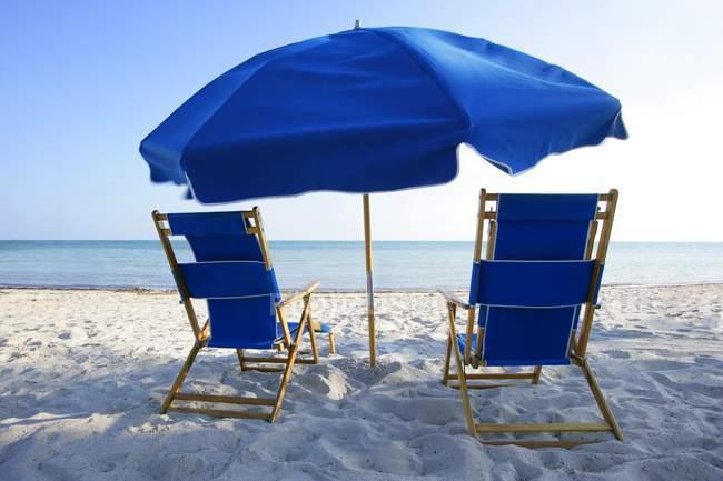 Пляжные стулья и зонтик — стоковое фото