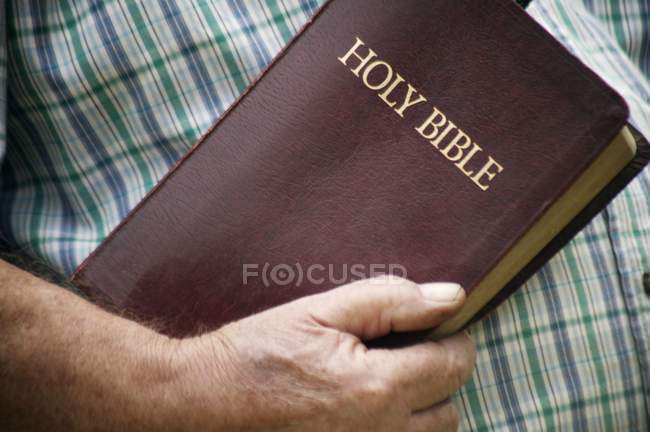Person in shirt Holding Bible — Stock Photo