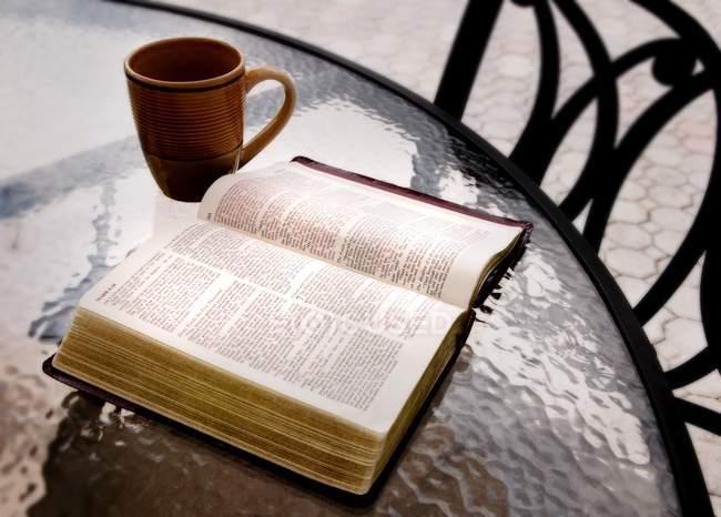 Открытая библия на столе — стоковое фото
