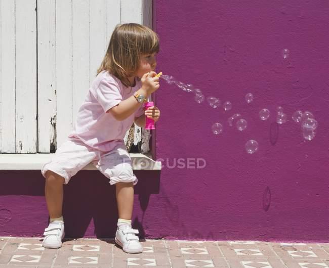 Vue de la fille assise sur la rue soufflant des bulles — Photo de stock