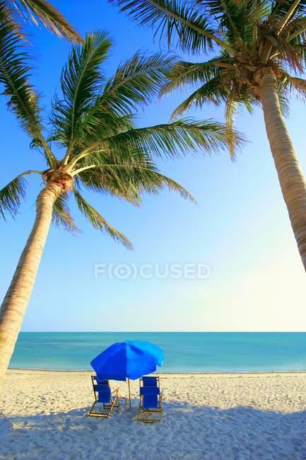 Стулья на песчаный пляж побережье — стоковое фото