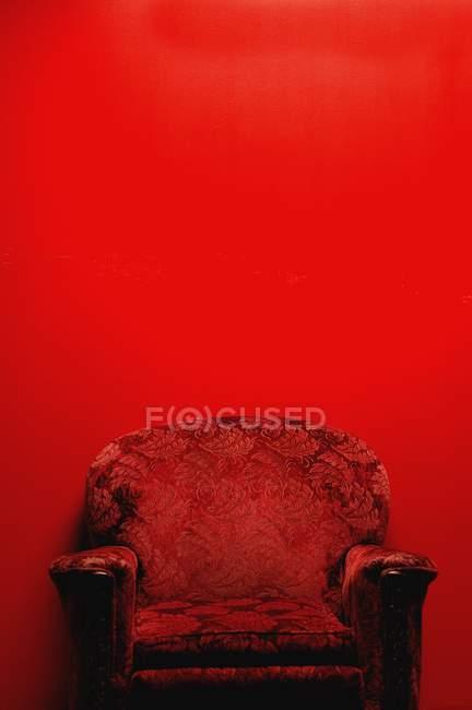 Sillón vintage frente al fondo rojo con espacio para copiar - foto de stock