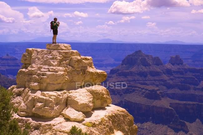 Hombre de pie sobre el pico rocoso - foto de stock