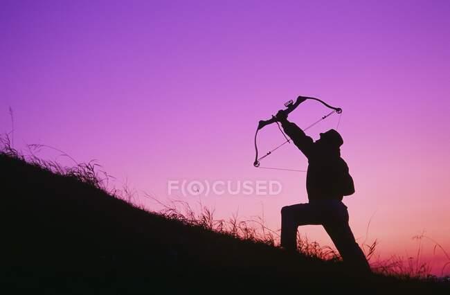 Silueta Archer contra el cielo del atardecer brillante - foto de stock