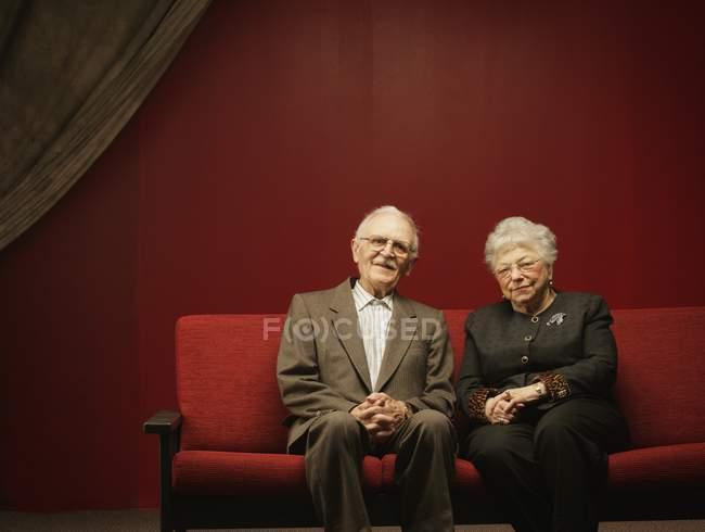 Coppia anziana dedicata seduta insieme sul divano rosso — Foto stock