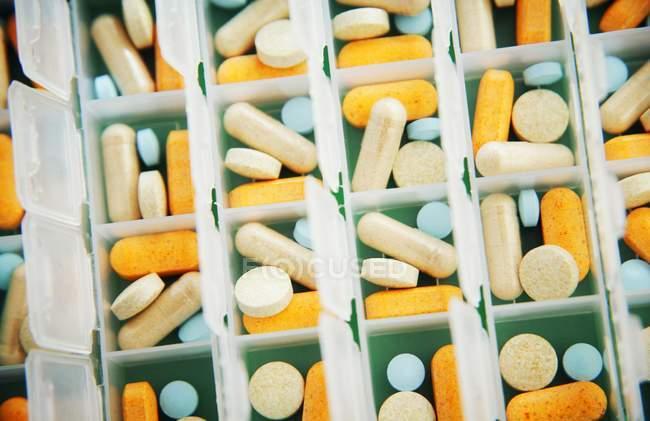 Различные медицинские таблетки сортируются в контейнере — стоковое фото