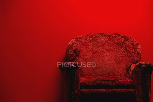 Vintage armchair in front of red background with copy space — Stock Photo