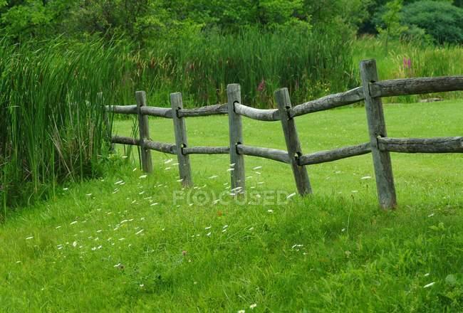Cerca de madeira na grama — Fotografia de Stock