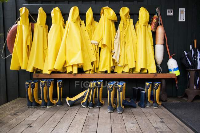 Yellow Raincoats And Rubber Boots Lined Up — Stock Photo