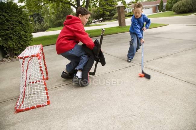 Два кавказька хлопчики грають вуличні хокею — стокове фото