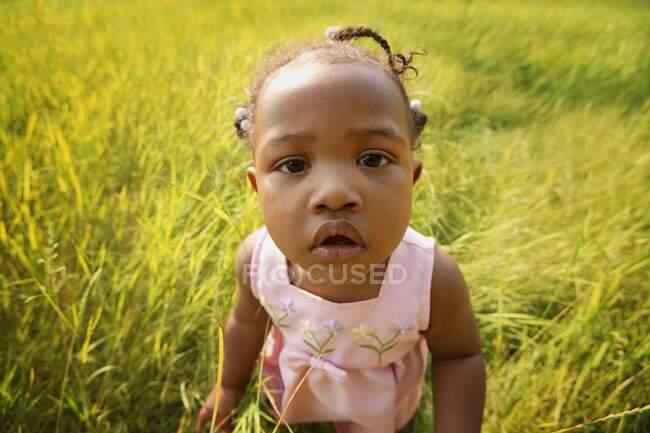 Vue rapprochée de l'adorable petit enfant Sur le terrain regardant la caméra — Photo de stock