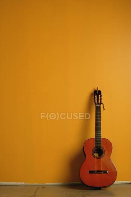 Vintage Akustikgitarre steht neben gelber Wand — Stockfoto
