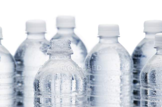 Fila de botellas de agua transparentes sobre fondo blanco - foto de stock