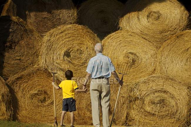 Grandfather And Grandson standing with pitchfork against hay bales — Stock Photo