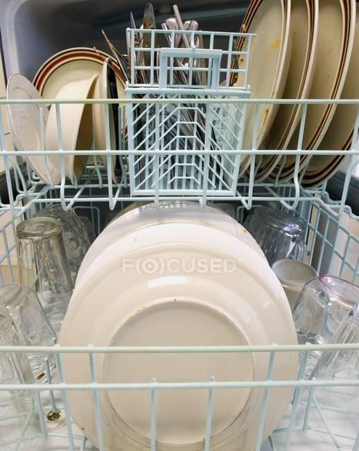 Lave-vaisselle ouvert avec cuillères, assiettes, fourchettes et couteaux — Photo de stock