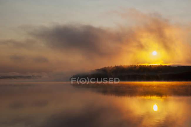 Nascer do sol sobre o lago deserto enevoado — Fotografia de Stock