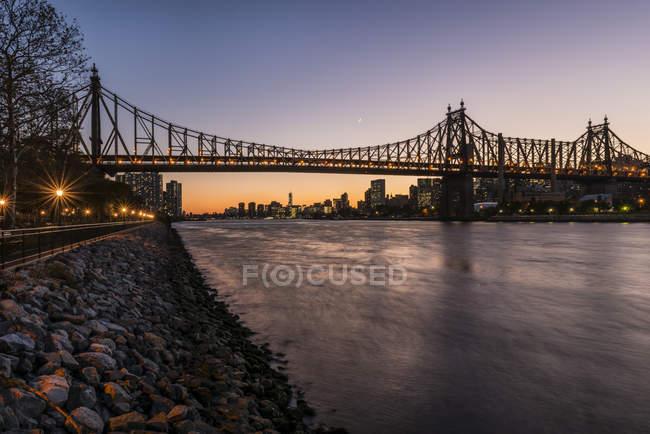 Puente al atardecer sobre el agua del río - foto de stock