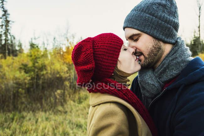 Giovane coppia che si tiene stretta e si bacia nel parco cittadino — Foto stock
