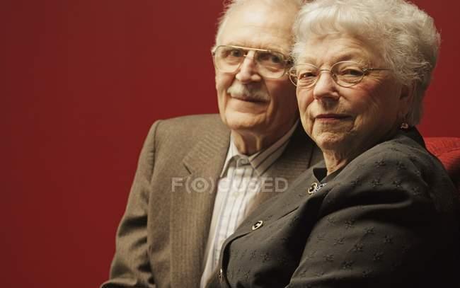 Довольный Пожилые супружеские пары, глядя на камеру на красном фоне — стоковое фото