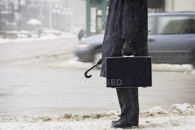 Imagem cortada de homem de negócios no casaco na rua nevada — Fotografia de Stock