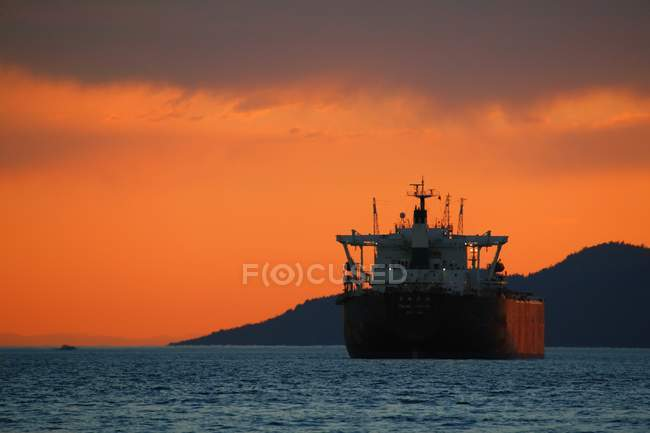 Freighter in ocean during sunset — Stock Photo