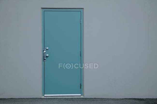Closeup view of blue door in grey wall with copy space — Stock Photo