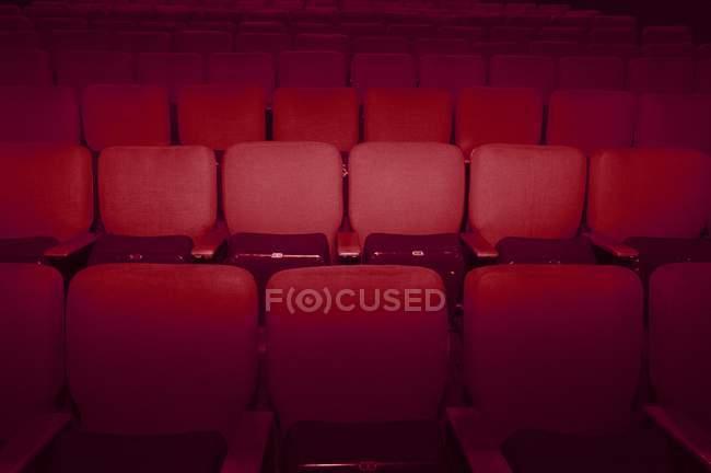 Ряды пустых красных стульев театра — стоковое фото