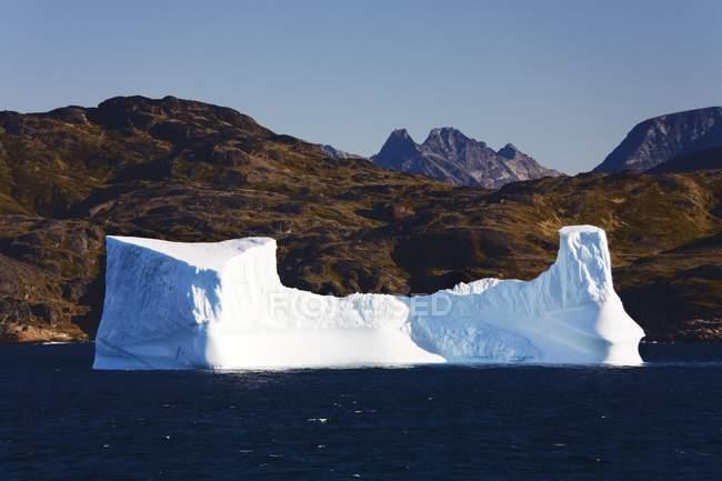 Eisberg im Wasser gegen Hügel — Stockfoto