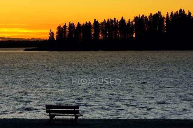 Закат и скамейка на берегу — стоковое фото