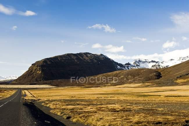Collines sur le champ et route — Photo de stock